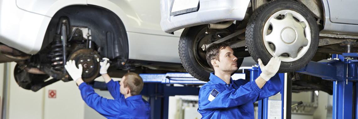 Auto mechanics servicing vehicles